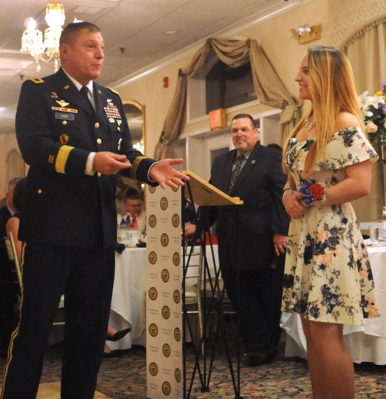 Our Community Salutes, a not-for-profit organization, hosted it's yearly induction ceremony in Patchogue, N.Y. to honor high school seniors who have recently enlisted into the military.  Maj. Gen. Troy D. Kok, commanding general of the U.S. Army Reserve's 99th Regional Support Command, presents Samantha Braband, who has enlisted in the Navy, a challenge coin. In the background stands event organizer Bob Vecchio. Vecchio is chairman of Our Community Salutes Brookhaven Town Chapter and is also the president of the Board of Education for the William Floyd school district of Suffolk County, N.Y.
