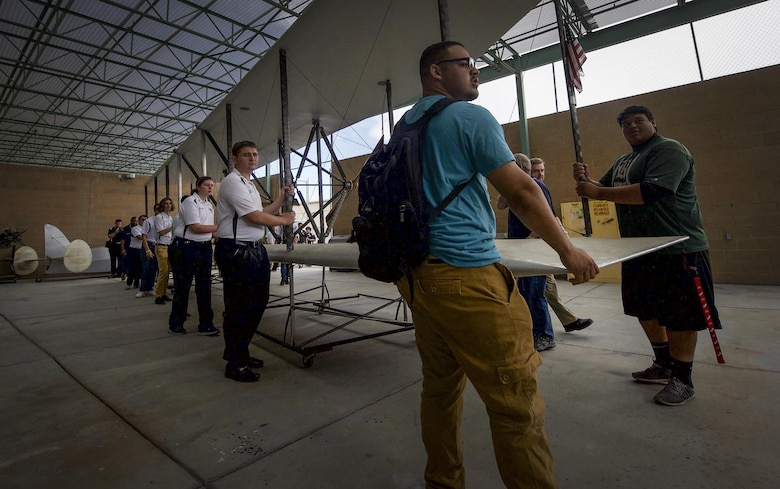 Aviation students move the wings of the USU Wright Flyer into the aviation lab of Rancho High School, May 15, 2017. Once assembled, the aircraft will make an appearance during the Aviation Nation air show and open house at Nellis Air Force Base, Nev., in November. (U.S. Air Force photo by Senior Airman Kevin Tanenbaum)