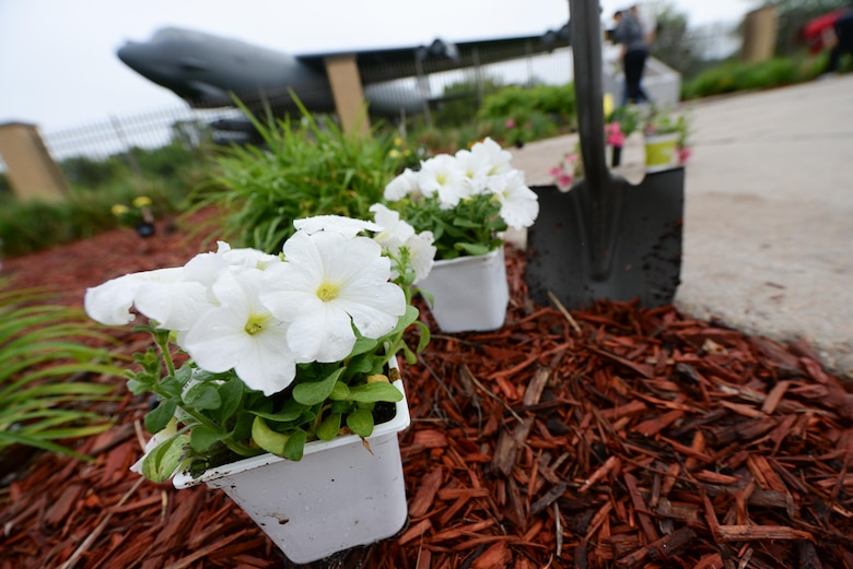 Members of the 55th Security Forces Association plant flowers and lay mulch outside the Kenney Gate at Offutt Air Force Base, Nebraska, May 10, 2017 during a beautification project. Airmen planted flowers, plants, grass seeds and spread mulch to make Offutt AFB look presentable. (U.S. Air Force photo by Zachary Hada)