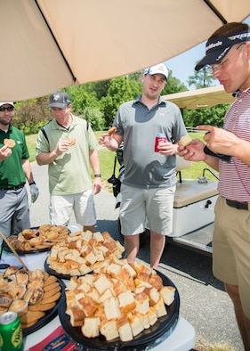 Participants of the 2017 spring Bluesuiters Golf Tournament take a break and enjoy some snacks from La Baguette Bakery May 17, 2017, 2016, at the Jonathan's Landing Golf Course in Magnolia, Delaware. Four different local businesses set up break stations throughout the 18 hole course. (U.S. Air Force photo by Mauricio Campino)