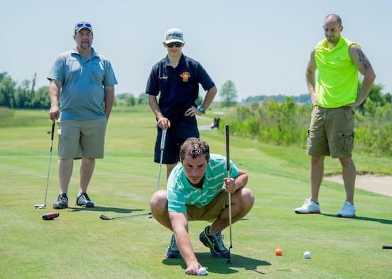 Dover realtor Anthony Lapinsky lines up a putt shot at the 2017 spring Bluesuiters Golf Tournament May 17, 2017, 2016, at the Jonathan's Landing Golf Course in Magnolia, Delaware. Team Dover Airmen are paired up with local civic and business leaders to build and maintain good community relations. (U.S. Air Force photo by Mauricio Campino)