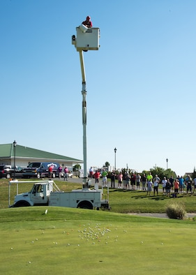 Golfers watch as balls are dropped from a maintenance vehicle at the 2017 spring Bluesuiters Golf Tournament May 17, 2017, 2016, at the Jonathan's Landing Golf Course in Magnolia, Delaware. Participants were able to purchase the numbered balls beforehand and the owner of the ball closest to the golf hole was awarded a cash prize. The truck was provided by ShureLine Electrical, one of the tournament sponsors. (U.S. Air Force photo by Mauricio Campino)