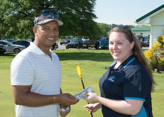 Cristal Brenneman, Central Delaware Chamber of Commerce Director of Special Events, awards Erol Gutierrez, shift manager at the Harrington Casino, prize money at the 2017 spring Bluesuiters Golf Tournament May 17, 2017, 2016, at the Jonathan's Landing Golf Course in Magnolia, Delaware. Gutierrez won the prize money when his golf ball landed closest to the putting hole. (U.S. Air Force photo by Mauricio Campino)