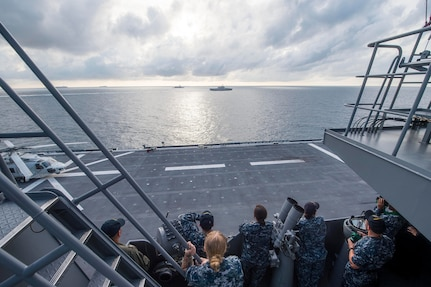 Sailors assigned to littoral combat ship USS Coronado (LCS 4) watch their ship maneuver alongside the Japan Maritime Self-Defense Force ship JS Izumo (DDH 183) while aboard for a personnel exchange as part of a passing exercise between the two navies, May 18, 2017. Coronado is on a rotational deployment in U.S. 7th Fleet area of responsibility, patrolling the region's littorals and working hull-to-hull with partner navies to provide 7th Fleet with the flexible capabilities it needs now and in the future.