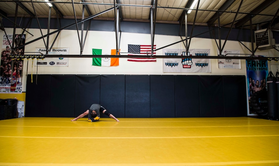 Airman 1st Class Raul Veliz, 90th Missile Security Forces Squadron response force leader, stretches before training at Trials Mixed Martial Arts gym in Fort Collins, Colo., May 5, 2017. Veliz makes the hour trip to Colorado four days a week to train. He is stationed at F.E. Warren Air Force Base, Wyo. (U.S. Air Force photo by Staff Sgt. Christopher Ruano)