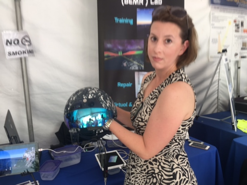 "Heidi Buck, director of the Army's Battlespace Exploitation of Mixed Reality Lab, presents a ""smart helmet"" that relays text-based commands and real-time imaging between the wearer and his or her commanding officer during DoD's Lab Day at the Pentagon, May 18, 2017. DoD photo by Rick Docksai"