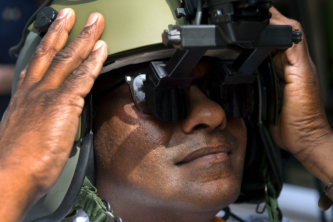 Aryankalayil Babu tries an Army aviation helmet with heads up display during the DoD Lab Day at the Pentagon, May 18, 2017. DoD photo by EJ Hersom