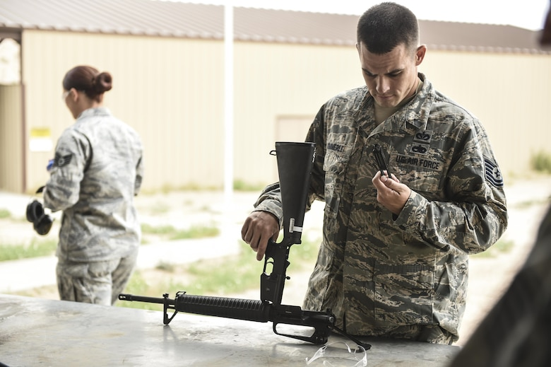Tech. Sgt. Benjamin Kimmerle, 49th Civil Engineer Squadron checks and assembles his weapon prior to the shooting competition held during National Police Week at Holloman Air Force Base, N.M. on May 15, 2017. National Police Week was established in 1962 by President John F. Kennedy to pay tribute to law enforcement officers who lost their lives in the line of duty for the safety and protection of others, according to the National Peace Officer's Memorial Fund website. Ceremonies are held annually in Washington D.C., as well as in communities across the nation. (U.S. Air Force photo by Staff Sgt. Stacy Jonsgaard)