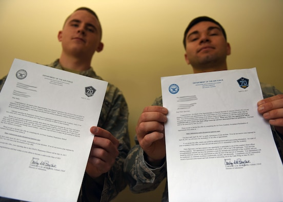 Senior Airman Justin Wilmoth, 30th Security Forces Squadron response force leader, and Airman 1st Class Pietro Sproviero De Paoli, 30th SFS armory technician, hold their Air Force Academy and Preparatory School acceptance letters, May 17, 2017, Vandenberg Air Force Base, Calif. Since its inception in 1954, the United States Air Force Academy has been considered one of the nation's most prestigious and selective universities. (U.S. Air Force photo by Senior Airman Kyla Gifford/Released)