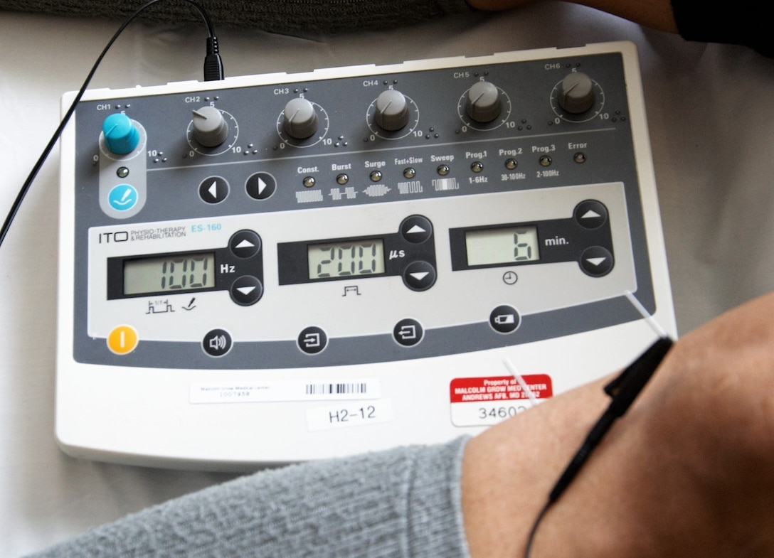 A licensed acupuncture specialist at the U.S. Air Force Acupuncture and Integrative Medicine Clinic can control the intensity of an electrical pulse while administering acupuncture treatment using the 6-channel electrical stimulator machine, show here, March 28, 2017 at Joint Base Andrews, Md. Wires connected to one needle inserted into a muscle knot and another contacting the knee bone carry an electrical pulse that can alleviate local leg pain and stimulate natural anti-pain chemicals throughout a patient's body. (U.S. Air Force photo by Staff Sgt. Joe Yanik)