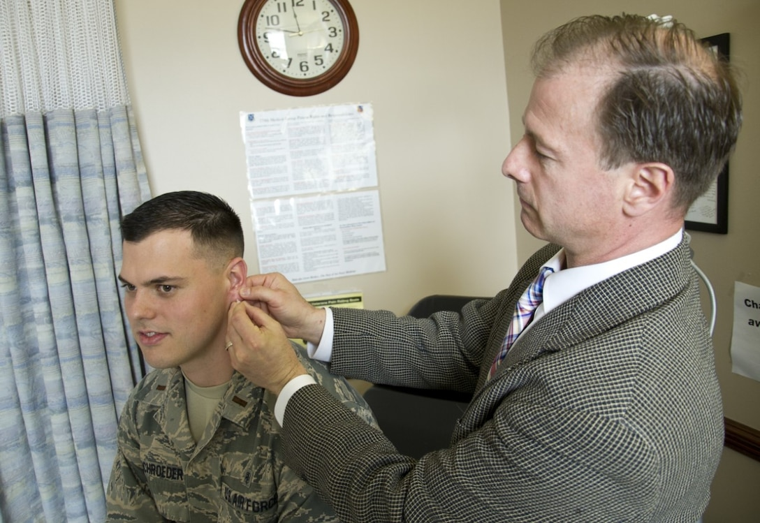 Dr. Thomas Piazza (right), U.S. Air Force Acupuncture Program director with the 779th Medical Group, inserts a semi-permanent acupuncture needle, or ASP, into the ear of 2nd Lt. Paul Schroeder, a Uniformed Services University student working with Dr. Piazza March 28, 2017, at Joint Base Andrews, Md. Piazza works with others at the Air Force Acupuncture and Integrative Medicine Clinic, the Department of Defense's only acupuncture therapy facility with a full time, licensed acupuncture staff of physicians. (U.S. Air Force photo by Staff Sgt. Joe Yanik)