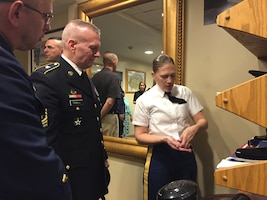 Army Staff Sgt. Ruth Hanks, the Tomb of the Unknowns sergeant of the guard, explains what the accouterments on her uniform mean to Army Command Sgt. Maj. John W. Troxell, the senior enlisted advisor to the chairman of the Joint Chiefs of Staff, and Master Chief Petty Officer of the Coast Guard Steven W. Cantrell at Arlington National Cemetery, Va., May 20, 2017. DoD photo by Jim Garamone