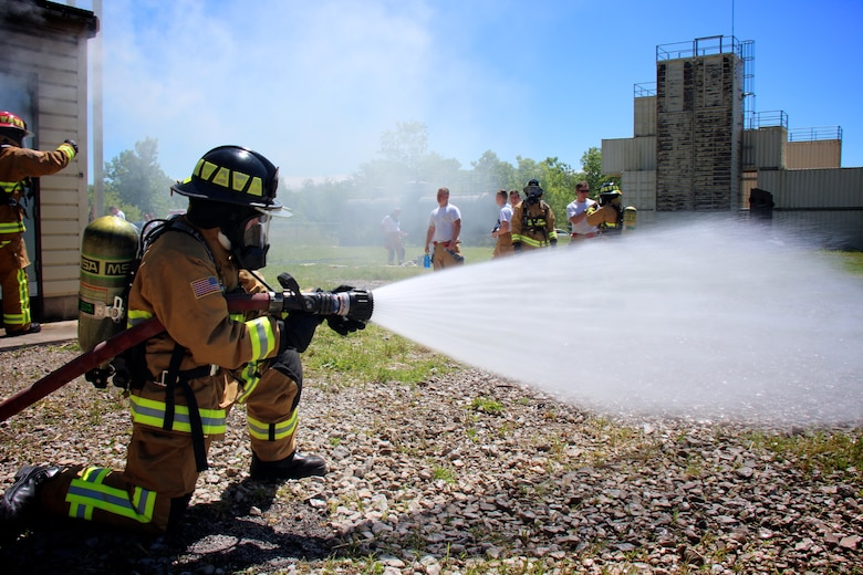 932nd Airlift Wing firefighters trained on core special skills particular to their jobs on May 21, 2017, at Scott Air Force Base, Illinois.   Airman Rachel Robert sprays water from the nozzle of he water hose connected to a fire truck  behind her, in preparation for her fellow firefighters to enter a smoke-filled building while searching for a simulated patient.  She ran this check on the system to ensure proper water pressure and availability of the resource in case it was needed to help put out a fire.   In the background, other 932nd Civil Engineering Squadron members suit up to take their turns and get the hot, dark, challenging experience. The 932nd Airlift Wing is part of 22nd Air Force, an Air Force Reserve Command unit located near Belleville, Illinois, and citizen airmen come to participate from 37 states.  (U.S. Air Force photo by Lt. Col. Stan Paregien)