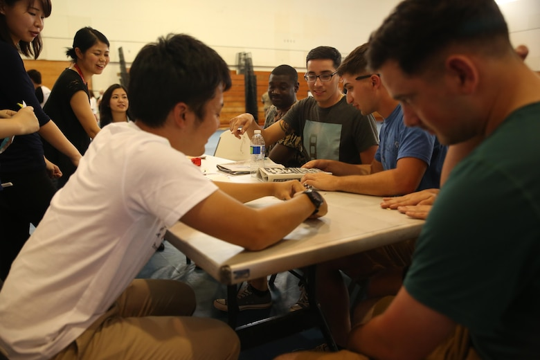 Marines with III Marine Expeditionary Force and Japanese students from Nikkei Business School in Okinawa City practice folding origami during the Okinawan-American Cultural Exchange Day, May 19, 2017, at House of Pain Fitness Center, on Camp Hansen, Okinawa, Japan. The Marines gave presentations about American culture and military operations to Japanese college students from Okinawa City and Naha, Okinawa. Marines with III MEF Headquarters Group hosted the cultural exchange day to strengthen bonds between the local community and service members, providing the two communities with the opportunity to converse and learn about each other's culture. (U.S. Marine Corps photo by Sgt. Tiffany Edwards)
