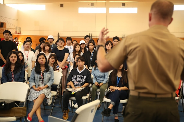 Lt. Col. Siebrand H. Niewenhous IV, commanding officer of Combat Logistics Battalion 31, 31st Marine Expeditionary Unit, addresses Japanese students from Nikkei Business School in Okinawa City during the Okinawan-American Cultural Exchange Day, May 19, 2017, at House of Pain Fitness Center, on Camp Hansen, Okinawa, Japan. The Marines gave presentations about American culture and military operations to Japanese college students from Okinawa City and Naha, Okinawa. Marines with III MEF Headquarters Group hosted the cultural exchange day to strengthen bonds between the local community and service members, providing the two communities with the opportunity to converse and learn about each other's culture. Niewenhous, a native of Pacific Grove, California, is a graduate of California State University. (U.S. Marine Corps photo by Sgt. Tiffany Edwards)