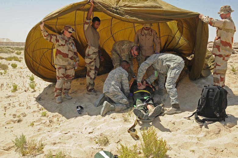 Members of the 380th Expeditionary Medical Group medical operations flight prepare a pilot for transport with the assistance of French security forces during a joint crash exercise at an undisclosed location in Southwest Asia, May 16, 2017. Coalition first responders worked together to provide joint response and care and to simulate how they would respond in the event of an aircraft mishap. [Faces of French personnel have been obscured at the request of l'Armée de l'air.] (U.S. Air Force photo by Staff Sgt. Marjorie A. Bowlden)
