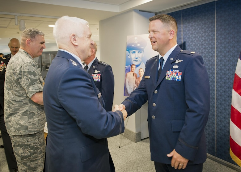Lt. Gen. L. Scott Rice, director of the Air National Guard congratulates Maj. John Hourigan, a 123rd Operations Support Squadron C-130 Hercules pilot, after a ceremony where Hourigan received the Koren Kolligian Jr. Trophy at the Pentagon, Washington, D.C., May 17, 2017. On July 15, 2016, Hourigan's aircraft began vibrating so badly that crew members were unable to communicate with each other through their headsets, read gauges or flight instruments. Hourigan quickly determined the source of vibration, implemented corrective action and executed an engine-out landing, saving the lives of all six crew members on board. (U.S. Air National Guard photo by Master. Sgt. Marvin R. Preston)
