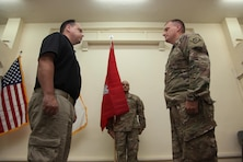 Col. Corey Spencer (right), commander of the U.S. Army Corps of Engineers – Transatlantic Division, Task Force Essayons, pauses after unfurling the unit guidon with Mr. Donny Davidson, Task Force Essayons deputy engineer for programs and project management (left), and Master Sgt. Eddie Rodriguez, Kuwait support cell non-commissioned officer-in-charge (center), during the Task Force Essayons activation ceremony, Friday, May 19, 2017 at Camp Taji, Iraq. (COMCAM Photo)
