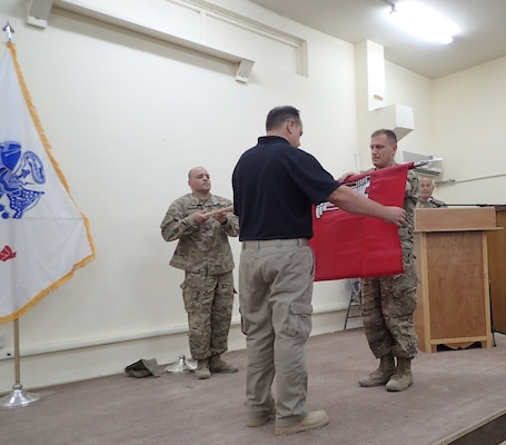 Col. Corey Spencer (right), commander of the U.S. Army Corps of Engineers – Transatlantic Division, Task Force Essayons, unfurls the unit guidon with Mr. Donny Davidson, Task Force Essayons deputy engineer for programs and project management (center), and Master Sgt. Eddie Rodriguez, Kuwait support cell non-commissioned officer-in-charge (left), during the Task Force Essayons activation ceremony, Friday, May 19, 2017 at Camp Taji, Iraq. (Submitted Photo)