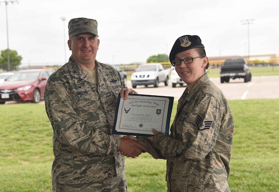 Staff Sgt. Natalie Whitt, 22nd Security Forces Squadron Armory NCO in charge, receives a certificate from Col. Albert Miller, 22nd Air Refueling Wing commander, May 18, 2017, at McConnell Air Force Base, Kan. Whitt earned the spotlight performer for the week of May 1-5. (U.S. Air Force photo/Airman 1st Class Erin McClellan)