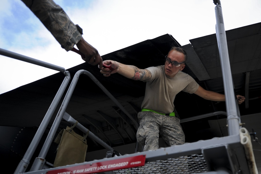 Airman 1st Class Jesse Coulter, a crew chief with the 4th Aircraft Maintenance Unit, grabs a mallet at Hurlburt Field, Fla., May 19, 2017. Coulter aided in the installation of a flat baffle on an AC-130U Spooky gunship. A flat baffle is used to improve aerodynamics and reduce turbulence during flight. (U.S. Air Force photo by Airman 1st Class Dennis Spain)