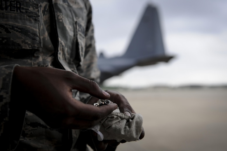 Airman 1st Class Anthony Hunter, a crew chief with the 4th Aircraft Maintenance Unit, removes screws from a small pouch at Hurlburt Field, Fla., May 19, 2017. Hunter helped install a new flat baffle to an AC-130U Spooky gunship. This part is installed on the wings of the aircraft and is replaced as needed. (U.S. Air Force photo by Airman 1st Class Dennis Spain)