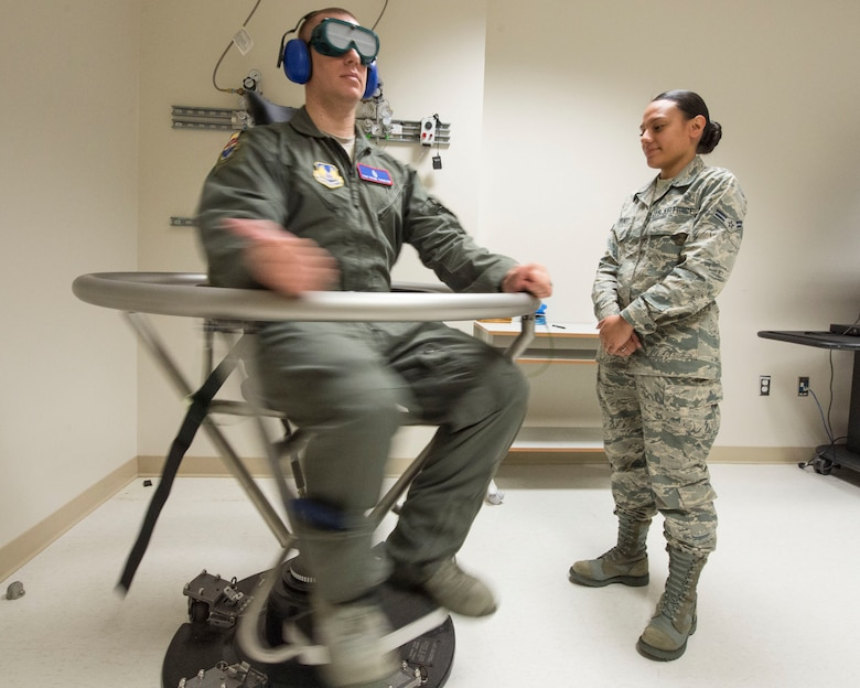 U.S. Air Force Tech. Sgt. Duane Thompson, USAF School of Aerospace Medicine operational physiology technician, spins during a Graveyard Spiral, as part of the Barany chair training for airsickness management program, while Airman 1st Class Agnes Cattaneo, USAF School of Aerospace Medicine operational physiology technician stands-by inside USAFSAM classroom at Wright-Patterson Air Force Base, Ohio, April 26, 2017.  The Barany chair is used as introductory spatial disorientation demonstrator and for rotational training as part of the airsickness management program. (U.S. Air Force photo/Michelle Gigante)