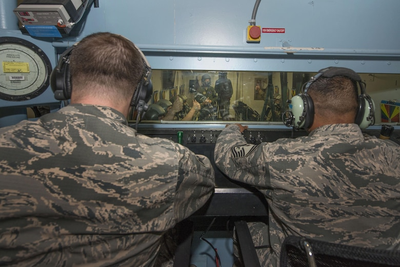 U.S. Air Force Tech. Sgt. Daniel Zerbe, (left) School of Aerospace Medicine operational physiology technician and Senior Master Sgt. Paul Johal (right), USAFSAM operational physiology superintendent, observe hypoxia demo training from the outside of the altitude hypobaric chamber during training at Wright-Patterson Air Force Base, Ohio, April 26, 2017. The hypobaric chamber provides a training system which replicates the effects of barometric pressure change on the human body. (U.S. Air Force photo/Michelle Gigante)