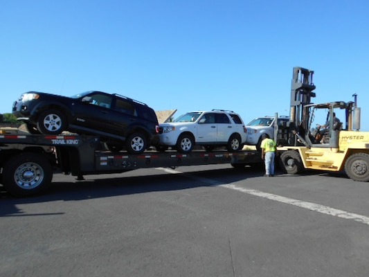 Workers load three 2008 Ford Escapes for their long journey from Hawaii to Moldova.