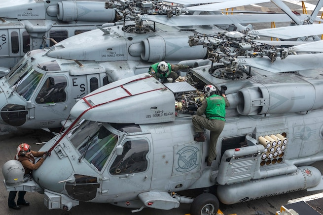 Sailors inspect an MH-60R Sea Hawk helicopter on the flight deck of the aircraft carrier USS Ronald Reagan in the waters south of Japan, May 18, 2017. The sailors are assigned to Helicopter Maritime Strike Squadron 77. Navy photo by Petty Officer 2nd Class Jamal McNeill