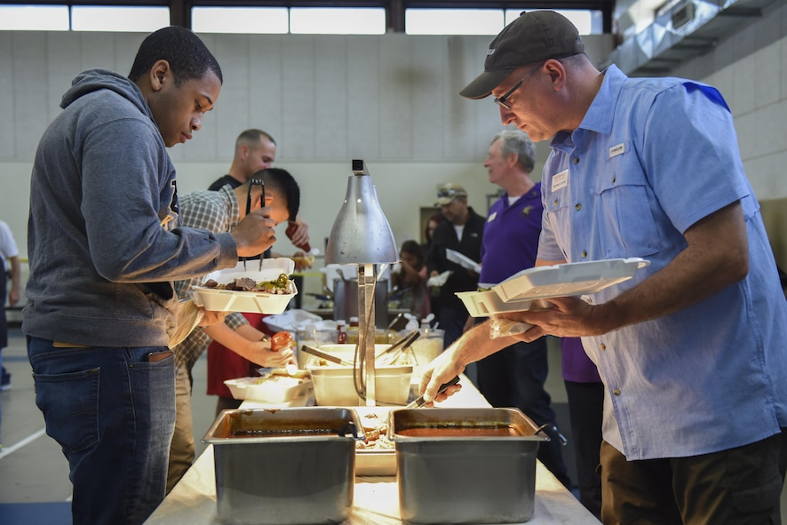 Goodfellow members and San Angelo residents plate their meals at the Goodfellow Appreciation Day at the Carswell Field House on Goodfellow Air Force Base, Texas, May 20, 2017. The event was sponsored by the city of San Angelo to show appreciation for Goodfellow and Goodfellow members. (U.S. Air Force photo by Airman 1st Class Chase Sousa/Released)