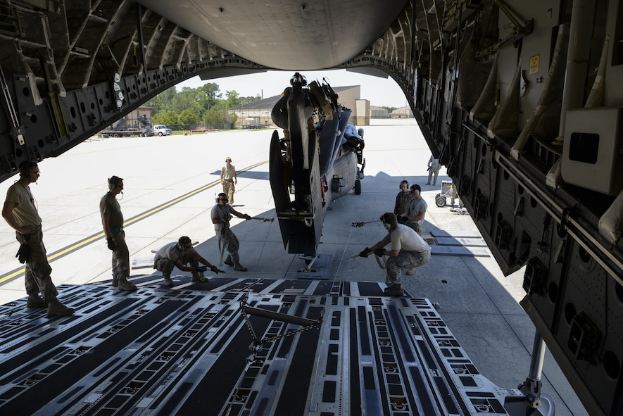 Members of the 723d Aircraft Maintenance Squadron, 41st Helicopter Maintenance Unit assigned to Moody Air Force Base, Ga., guide an HH-60G Pave Hawk search and rescue helicopter onto a 3d Airlift Squadron C-17 Globemaster III May 15, 2017, at Moody AFB. Airmen applied constant pressure on the towlines to direct the helicopter and also ensure the winch maintained tension. (U.S. Air Force photo by Senior Airman Aaron J. Jenne)