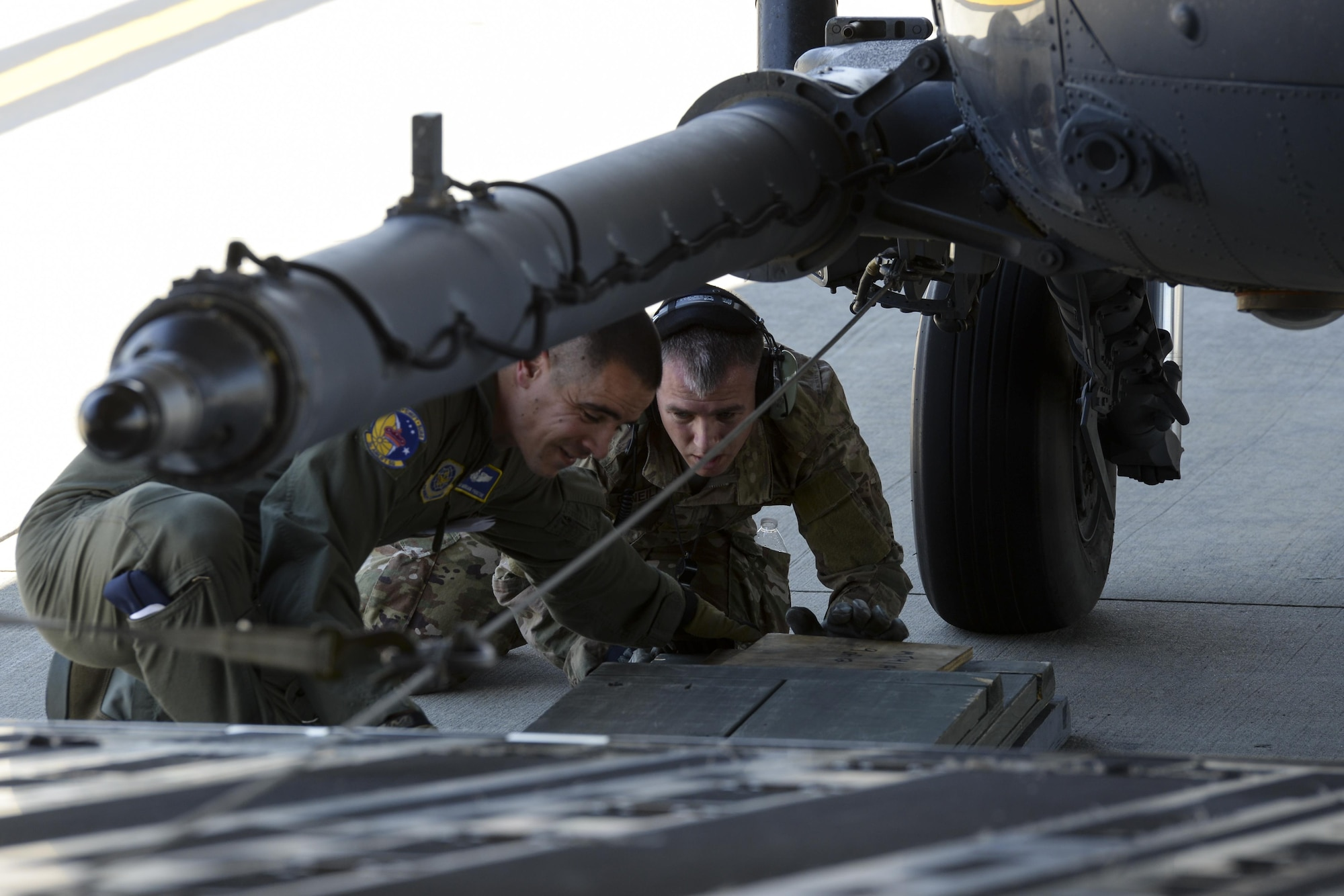 Tech. Sgt. Brendan Proctor, 3d Airlift Squadron loadmaster, and Staff Sgt. Sean O'Neill, 723d Aircraft Maintenance Squadron, 41st Helicopter Maintenance Unit crew chief assigned to Moody Air Force Base, Ga., ensure proper block placement prior to loading an HH-60G Pave Hawk search and rescue helicopter onto a 3d AS C-17 Globemaster III May 15, 2017, at Moody AFB. Special care was taken to not damage either aircraft when loading. (U.S. Air Force photo by Senior Airman Aaron J. Jenne)