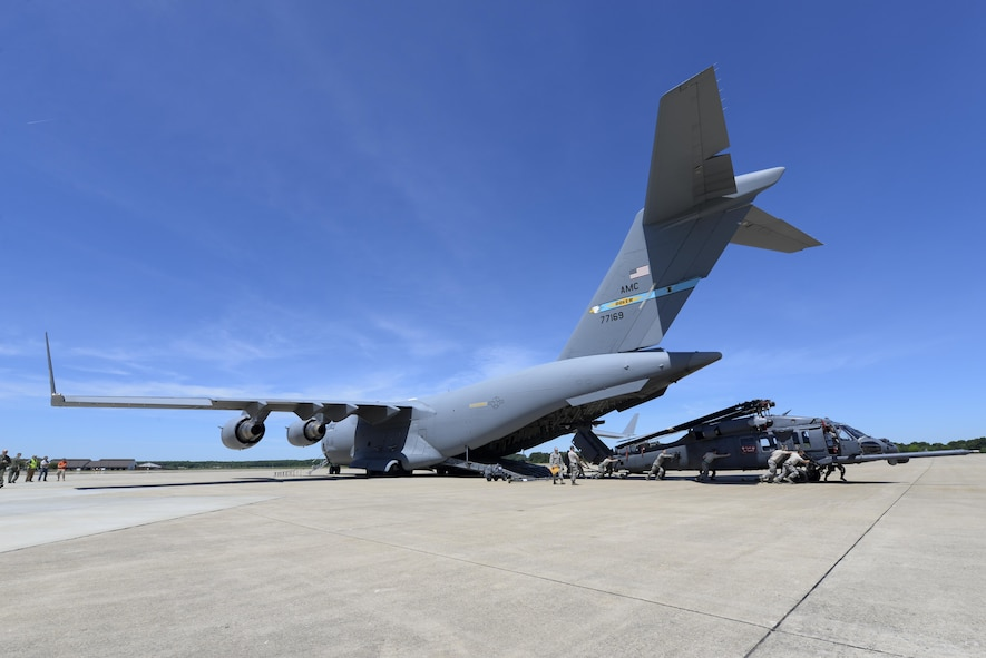 One of Team Dover's C-17 Globemaster IIIs sets on the flightline as an HH-60G Pave Hawk search and rescue helicopter is offloaded May 16, 2017, at Langley Air Force Base, Va. The C-17 transported 2 helicopters and 40 Airmen from Moody AFB, Ga., to Langley AFB where they participated in Exercise RAPID RESCUE. (U.S. Air Force photo by Senior Airman Aaron J. Jenne)