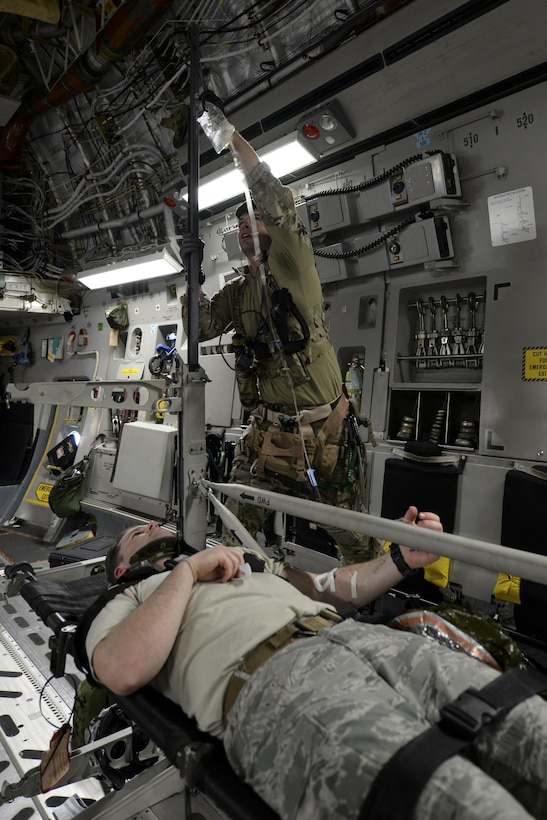 Senior Airman Jay Vinehout, 38th Rescue Squadron pararescueman assigned to Moody Air Force Base, Ga., hangs an IV bag for a simulated patient May 17, 2017, during Exercise RAPID RESCUE aboard a 3d Airlift Squadron C-17 Globemaster III. The plane flew around the coast of Va. for an hour while the 38th RS members practiced advanced medical techniques intended to stabilize patients with severe injuries. (U.S. Air Force photo by Senior Airman Aaron J. Jenne)