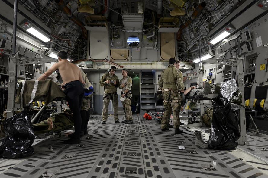 A team of pararescuemen assigned to the 38th Rescue Squadron, Moody Air Force Base, Ga., tend to the simulated injuries of three Airmen May 17, 2017, during Exercise RAPID RESCUE aboard a 3d Airlift Squadron C-17 flying over the coast of Va. When deployed, pararescuemen routinely support aeromedical evacuations aboard cargo aircraft. (U.S. Air Force photo by Senior Airman Aaron J. Jenne)