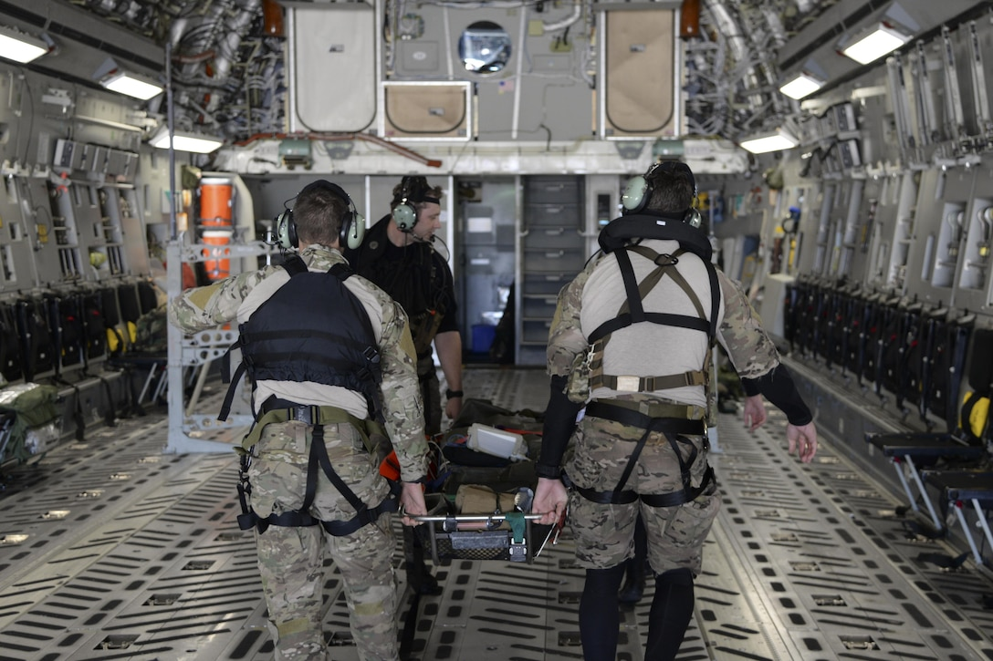Members of the 38th Rescue Squadron assigned to Moody Air Force Base, Ga., carry an Airman with simulated injuries May 17, 2017, aboard a 3d Airlift Squadron C-17 Globemaster III during Exercise RAPID RESCUE. A few minutes later, the aircraft departed from Langley AFB, Va., simulating an aeromedical evacuation for three injured Airmen. (U.S. Air Force photo by Senior Airman Aaron J. Jenne)