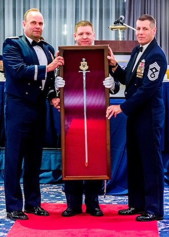 Brig. Gen. Keith M. Givens, the 17th Air Force Office of Special Investigations Commander, AFOSI Command Chief Master Sgt. Christopher VanBurger and Chief Master Sgt. Davy Davis pose with the personal sword presented to General Givens during his Order of the Sword Induction ceremony May 19, 2017, at Joint Base Anacostia-Bolling. The ceremonial sword is displayed at AFOSI Headquarters, Quantico, Va. (U.S. Air Force photo/Michael Hastings)