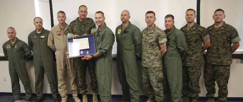 Maj. Gen. Daniel O'Donohue, fourth from left, 1st Marine division commanding general, awards Col. Michael Borgschulte, fifth from left, commanding officer of Marine Aircraft Group (MAG) 39, and the MAG-39 squadron commanding officers, a certificate of honorary membership at Marine Corps Air Station Camp Pendleton, Calif., May 15. 1st MARDIV recognized MAG-39 as an honorary member for continuing to support I MEF ground Marines and continuously working toward more advanced Marine air-ground task force integration. (U.S. Marine Corps photo by Lance Cpl. Jake M.T. McClung/Released)