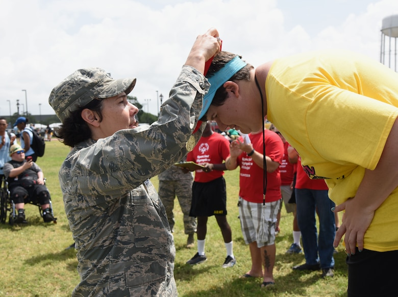 Col. Jeannine Ryder, 81st Medical Group commander, presents a medal to Jennifer Didlake, Area 17 athlete, during the Special Olympics Mississippi 2017 Summer Games May 20, 2017, on Keesler Air Force Base, Miss. Founded in 1968, Special Olympics hosts sporting events around the world for people of all ages with special needs to include more than 700 athletes from Mississippi. (U.S. Air Force photo by Kemberly Groue)