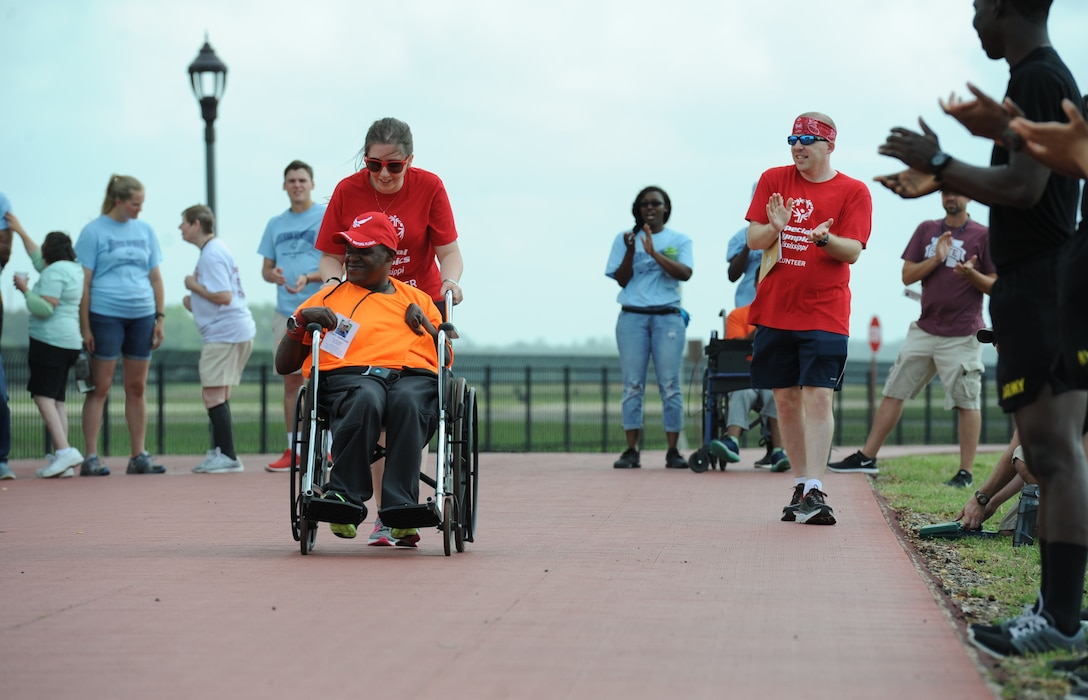 Senior Airman Holly Mansfield, 81st Training Wing public affairs photojournalist, pushes Gary Anderson, Area 12 athlete, during the 25-meter assisted walk during the Special Olympics Mississippi 2017 Summer Games May 20, 2017, on Keesler Air Force Base, Miss. Keesler hosted more than 3,200 athletes, directors, coaches, family members and volunteers spanning over 16 regions across Mississippi for the 31st year. (U.S. Air Force photo by Kemberly Groue)