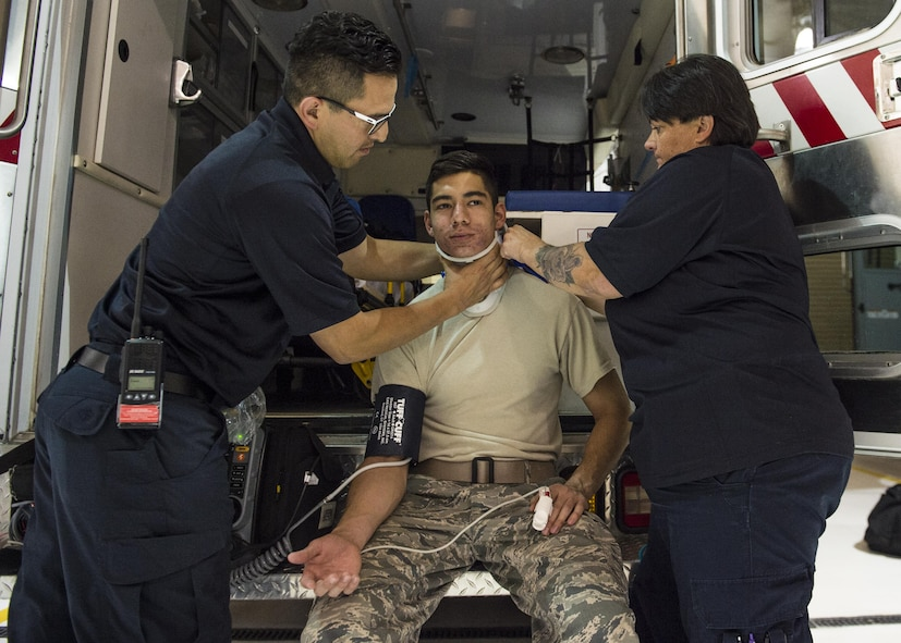 Hector Maldonado, a 49th Medical Operations Squadron emergency medical technician-Intermediate, and Annette Dunlap, the 49th MDOS area project manager and a paramedic, perform an emergency response simulation on a volunteer for National Emergency Medical Services week at Holloman Air Force Base, N.M. on May 18, 2017. National EMS week was established in 1974, as a means to honor EMS practitioners and their contributions to families and communities across the United States. Holloman's EMS practitioners work 24-hour shifts. The most basic function of their job involves responding to 911 and flight line emergencies. (U.S. Air Force photo by Airman 1st Class Alexis P. Docherty)