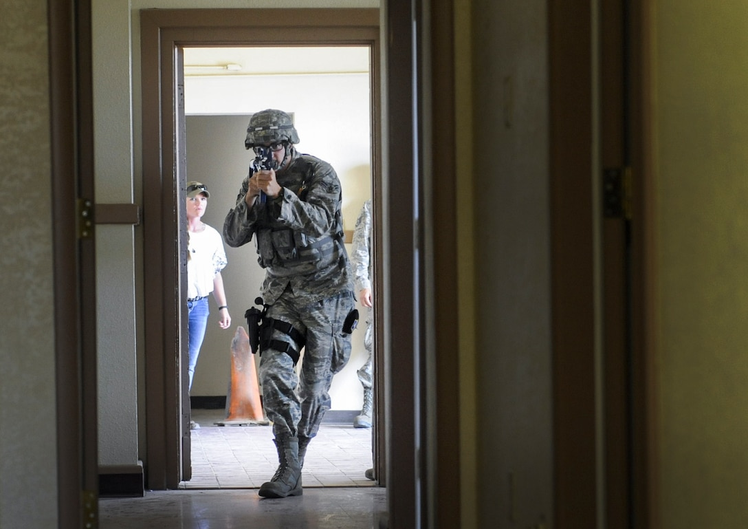 Airman 1st Class Nicolus Thompson, 99th Security Forces Squadron member, enters a simulated active shooter scenario in Area II on Nellis Air Force Base, Nev., May 17, 2017. Defenders of the 99th SFS immediately followed established procedures to respond to and neutralize the simulated threat. (U.S. Air Force photo by Senior Airman Kevin Tanenbaum/Released)