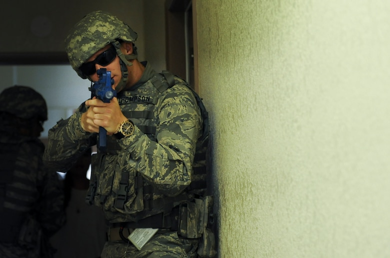 Airman 1st Class Nicolus Thompson, 99th Security Forces Squadron member, covers the front of a formation during a simulated active-shooter scenario in Area II on Nellis Air Force Base, Nev., May 17, 2017. The 99th SFS provides flight line security, police services, antiterrorism and force protection for Nellis and Creech AFBs. (U.S. Air Force photo by Senior Airman Kevin Tanenbaum/Released)