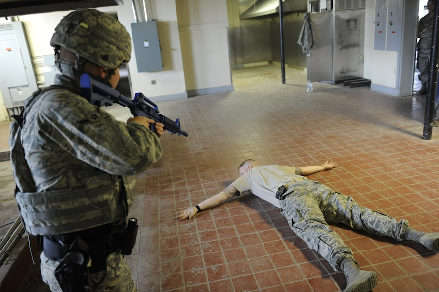 An Airman assigned to 99th Security Forces Squadron apprehends a simulated active-shooter during a training simulation in Area II on Nellis Air Force Base, Nev., May 17, 2017. The squadron is responsible for ensuring the safety of all base weapons, property and personnel from hostile forces. (U.S. Air Force photo by Senior Airman Kevin Tanenbaum/Released)