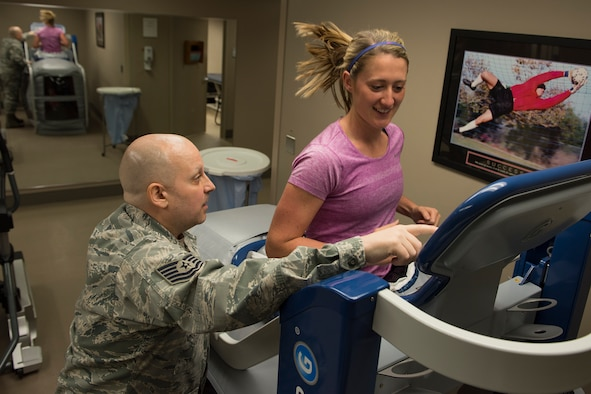 """Tech. Sgt. Jesse Myers, 92nd Medical Group Physical Therapy and Orthodontics flight chief, shows Lauren Buyer, 92nd MDG physical therapist, how to operate and use all the features of the """"Alter G"""" treadmill April 20, 2017 at Fairchild Air Force Base, Washington. The Alter G treadmill uses a pressurized chamber on the lower body to create buoyancy, lessening the impact of the user's steps and allowing running to be less painful. (U.S. Air Force Photo / Airman 1st Class Ryan Lackey)"""