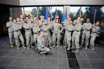 Col. Robyn Slade (right), 50th Space Wing senior individual mobilization augmentee to the commander, poses with a joyful, freshly graduated First-Term Airman's Course class at Schriever Air Force Base, Colorado, December 9, 2016. Slade attended many FTAC graduations in her time as IMA to the commander. (U.S. Air Force photo/Chris DeWitt)