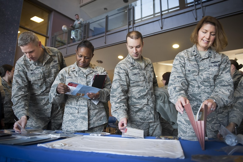 Col. Robyn Slade (right), 50th Space Wing senior individual mobilization augmentee to the commander, browses the contents of the 50 SW time capsule, opened at Schriever Air Force Base, Colorado, January 31, 2017. Being IMA to the commander of the wing during this moment in history is one of the many ways Slade has served the 50 SW during her last years of service. (U.S. Air Force Photo/Dennis Rogers)