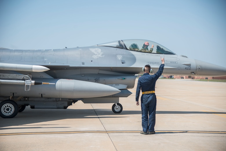"U.S. Air Force Airman 1st Class Evan Wilcox, a 35th Maintenance Group dedicated crew chief, holds up the 14th Fighter Squadron ""wood"" symbol while a pilot taxis at Kunsan Air Base, Republic of Korea, May 19, 2017. Wilcox had to trouble shoot an issue on the aircraft that required a pilot to test the system, ensuring it worked properly once repaired. (U.S. Air Force photo by Senior Airman Brittany A. Chase)"