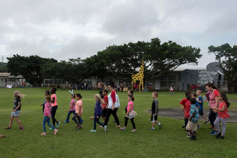 Children from Kadena Elementary School walk from one educational booth to another May 22, 2017, at Kadena Air Base, Japan. The school's English as a Second Language team presented 12 stations representing the Guinness Book of World Records to the whole school. (U.S. Air Force photo by Senior Airman John Linzmeier)